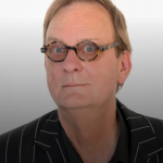 head shot of peter goers - black top, hair receding, and glasses with a round frame